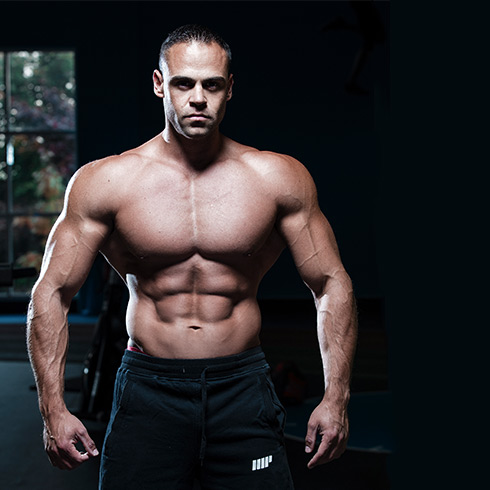 ragazzo muscoloso bodybuilder in piedi con pantaloni lunghi neri