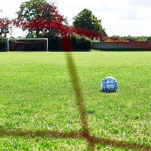 pallone da calcio in mezzo a campo da calcio visto dalla porta