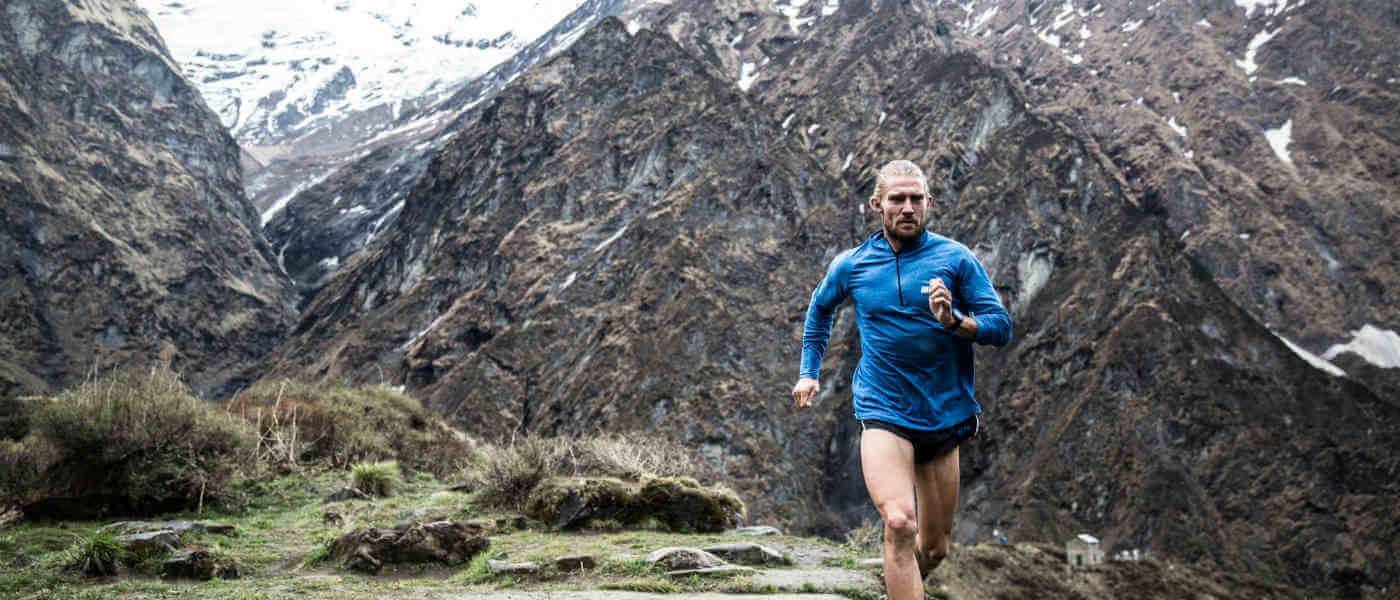 ragazzo biondo in pantaloncini corti e felpa che corre in montagna