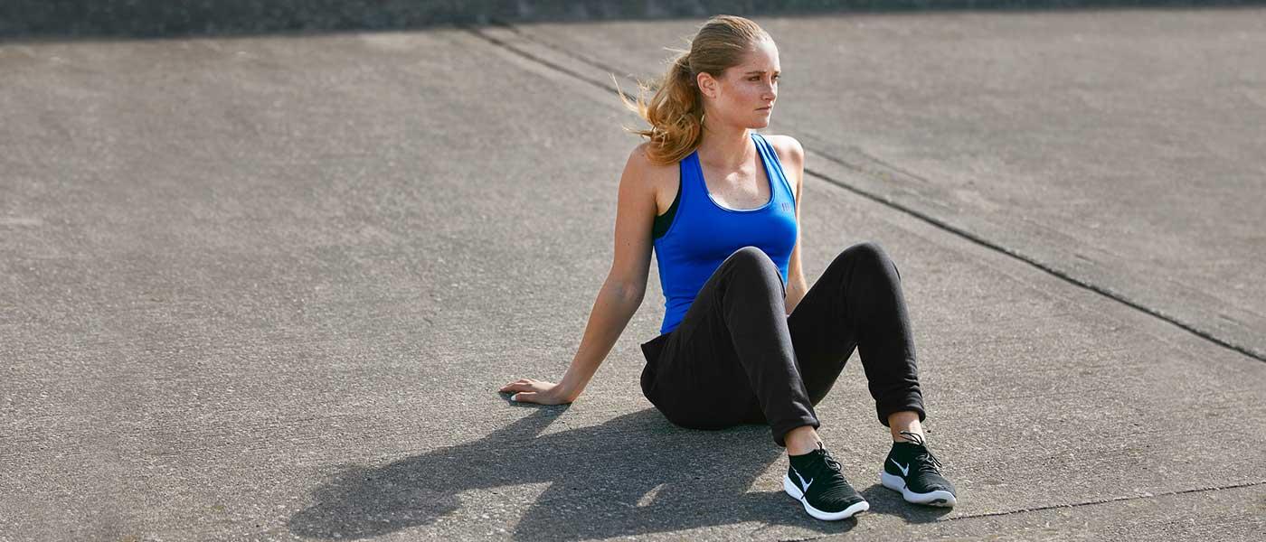 ragazza atletica bionda con canottiera blu seduta sulla strada