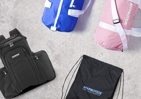 Presentasjon av myprotein treningsposer, herunder blått og rosa fat poser, trekke-streng treningsbagen, og ryggsekk