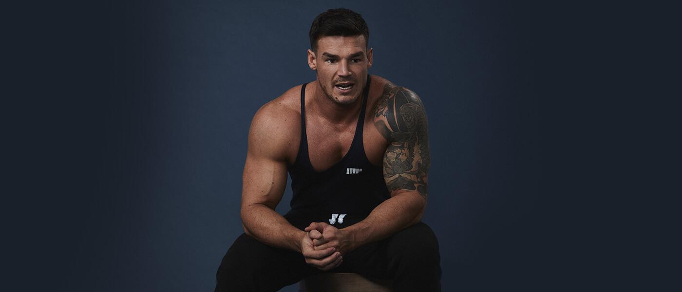 Mann fitness modell sitter i svart myprotein stringer og leggings