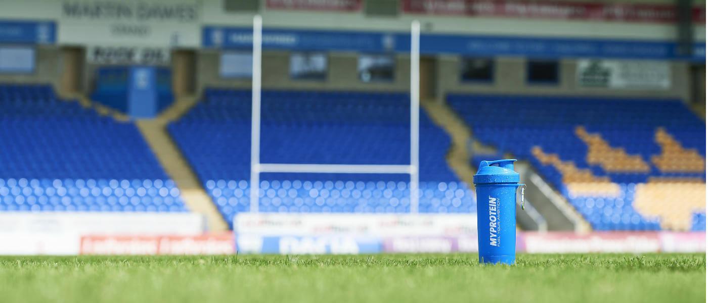 Blue myprotein shaker op rugbyveld met de horizontale streep in de achtergrond