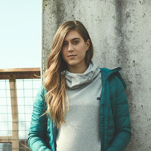 vrouwelijk model presentatie myprotien grijze hoodie en lichtgewicht turquoise puffer jacket