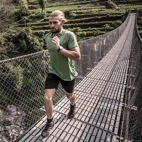 Mężczyzna sportowiec wytrzymałość biegnie przez most w zielonym wydajności myprotein koszulce