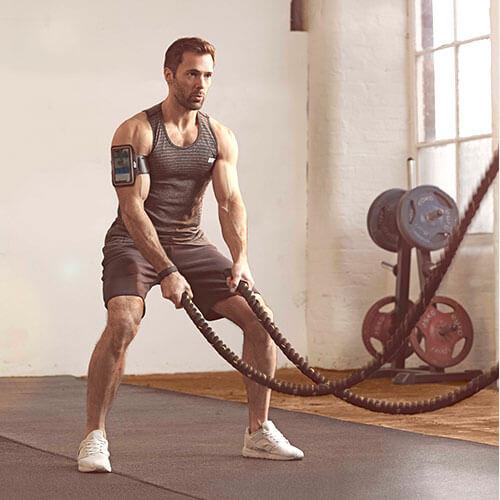 mężczyzna sportowiec w odzieży myprotein ćwiczący z linami bojowymi