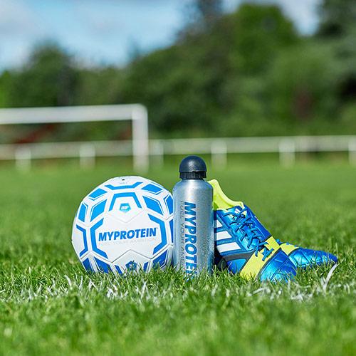 Myprotein voetbal, fles water en voetbalschoenen op gras voetbalveld