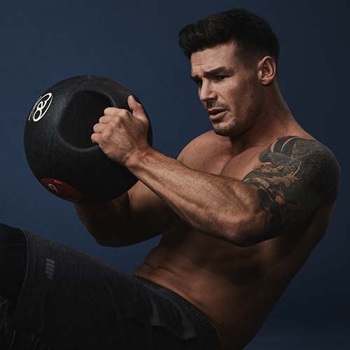 Atleta a fazer exercício no ginásio com uma bola pesada