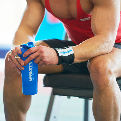 male athlete holding a protein shaker