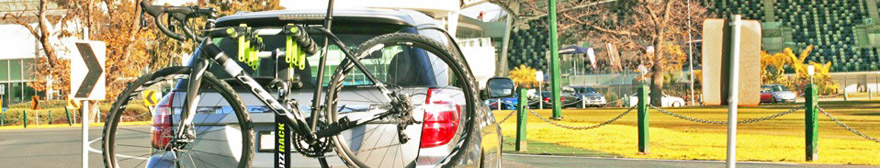 a road bike attached to the back of a car on a buzz rack