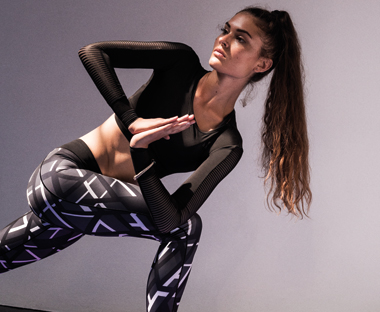 Female in lunge position modelling black patterned adidas leggings and a long sleeved black adidas cropped top