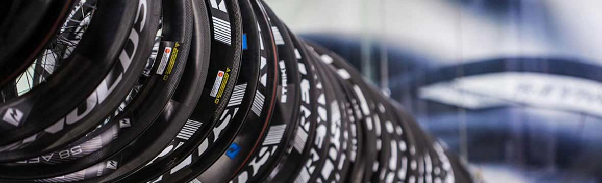 A row of bike wheels hanging in a workshop
