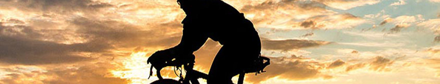silhouette of a cyclists riding in the sunset