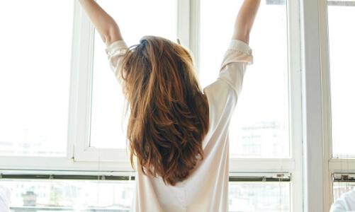 kvinde kigger ud af vinduen om morgen