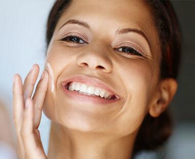 Kvinde som smør creme på ansigtet