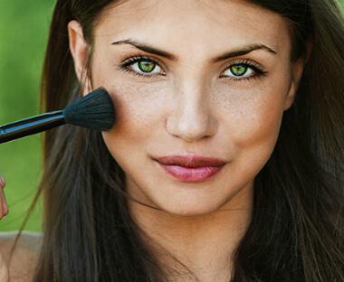 pige lægger makeup på kinden