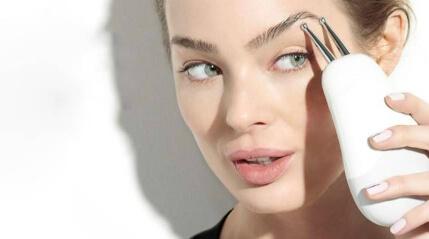 model bruger NuFace produkt på ansigtet