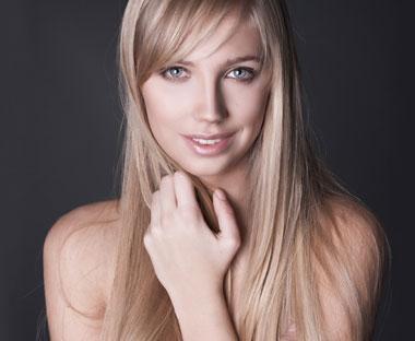 pige med blond hår, med hånden op til ansigtet